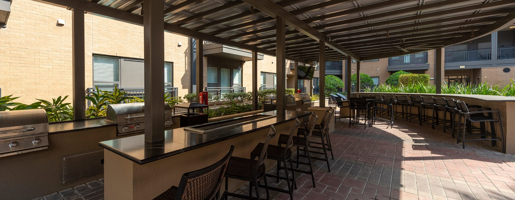 outdoor kitchen pavilion featuring four grill stations, circular bar and big screen TV